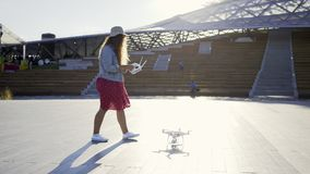 Woman prepare launch drone in park. Side view of casual young woman walking on pavement in modern park with quadcopter. Girl put drone and prepare to launch with stock video
