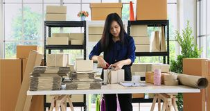 Woman prepare parcel post for send to customer. Young good looking Asian dark brown hair woman packing parcel post, prepare for send to her customer stock video footage