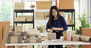 Woman prepare parcel post for send to customer. Young good looking Asian dark brown hair woman wrapping parcel post, prepare for send to her customer stock footage