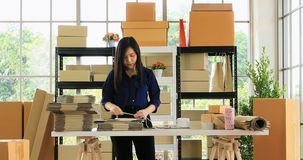 Woman prepare parcel post for send to customer. Zoom out scene video of young good looking Asian dark brown hair woman wrapping parcel post, prepare for send to stock video footage