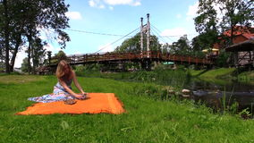 Woman prepare picnic place on orange plaid rug near river water stock video footage