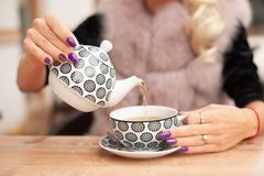 Woman prepare tea on bar terace hold teapot in her hands in ear. Ly autumn stock photography