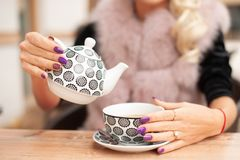 Woman prepare tea on bar terace hold teapot in her hands in ear. Ly autumn royalty free stock image