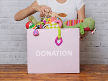Woman prepare to donate toys in charity shop. Girl prepare to donate toys in charity shop Royalty Free Stock Photos