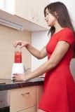 Woman prepares a fruit drink Stock Photos