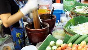 A woman prepares green papaya salad stock video