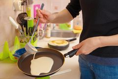 A woman prepares pancakes, pours the dough on a hot frying pan stock image