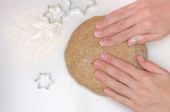 Woman prepares rye dough for baking. On the table poured white flour and moulds for cookies Stock Photos