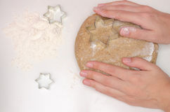 Woman prepares rye dough for baking. On the table poured white flour and moulds for cookies Stock Photo
