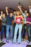 Woman prepares for throw ball friends it encourage. Woman prepares for throw ball in bowling and friends it encourage, focus on girl in center Royalty Free Stock Images