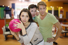 Woman prepares to throw of ball; men look Stock Photography