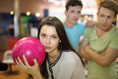 Woman prepares to throw of ball; men look at her royalty free stock photo