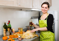 Woman preparing capon indoors. Portrait of smiling young brunette in apron preparing capon at home kitchen Royalty Free Stock Photos