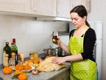 Woman preparing capon indoors Stock Images