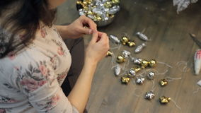 Woman preparing Christmas decorations ties ribbons to decorate studio. Top view of Decorator brunette worker tying ribbon on golden silver colored balls stock video