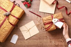 Woman preparing Christmas gifts. On wooden background, top view Royalty Free Stock Images