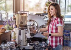 Woman preparing coffee with machine in cafe royalty free stock image