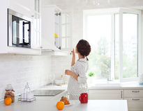 Woman preparing a cup of coffee in her kitchen wearing pajamas Stock Image