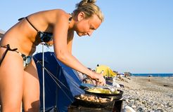 Woman preparing dinner near the sea Stock Photography