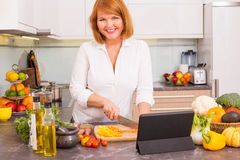 Woman preparing dinner from recipe in tablet. Happy woman preparing dinner from recipe in tablet Royalty Free Stock Photography