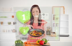 Woman preparing dinner using futuristic interface. In the kitchen at home Royalty Free Stock Photography