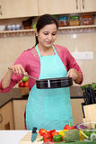 Woman preparing a dish in her kitchen Royalty Free Stock Photography