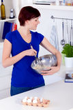 Woman preparing dough for a cake and checking the receipe Stock Image