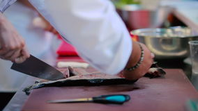 The woman preparing a fish at the kitchen. Close-up: the woman preparing a fish at the kitchen of the restaurant. Chef teaches how to cut a knife fish bones in stock footage