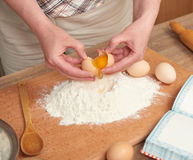 Woman preparing flour for baking on a wooden background. Raw food and kitchen utensils. Hands and food closeup. Break an egg, cook Stock Photo
