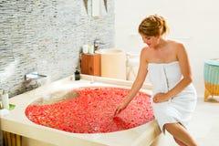 Woman preparing flower bath. Beautiful woman preparing flower bath Stock Photography