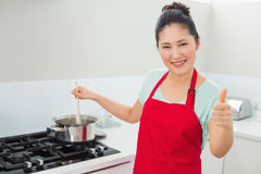 Woman preparing food while gesturing thumbs up in kitchen Royalty Free Stock Image