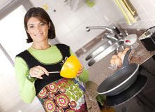 Woman preparing food at the kitchen Stock Photos