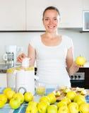 Woman preparing fresh apple juice. Young cheerful woman preparing fresh apple juice in domestic kitchen Stock Image