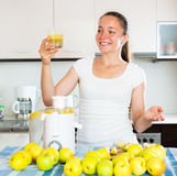 Woman preparing fresh apple juice. Young woman preparing fresh apple juice in domestic kitchen Stock Photo
