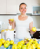 Woman preparing fresh apple juice. Young happy woman preparing fresh apple juice in domestic kitchen Stock Images