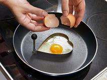 Woman preparing fried eggs in heart form Royalty Free Stock Photos