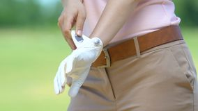 Woman preparing for golf tournament wearing special leather glove on hand. Stock footage stock video