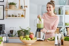 Woman preparing green smothie. Happy woman preparing healthy green smoothie in her kitchen Royalty Free Stock Image