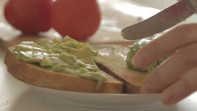 Woman preparing healthy breakfast with avocado on roasted bread, eggs and tomato. Woman preparing health breakfast in the kitchen in the morning hours by stock video