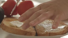 Woman preparing healthy breakfast with avocado on roasted bread, eggs and tomato. Woman making health breakfast in the kitchen in the morning hours by spreading stock video footage