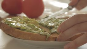 Woman preparing healthy breakfast with avocado on roasted bread, eggs and tomato. Woman making health breakfast in the kitchen in the morning hours by spreading stock video