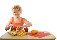 Woman preparing healthy fruit salad. Young woman preparing healthy food dessert with a big smile stock photography