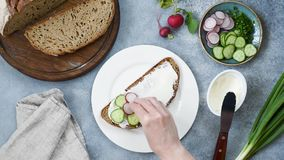 Woman preparing healthy toast with cucumber, radish, cream cheese. Woman preparing healthy breakfast toast with cucumber, radish, cream cheese. Table top view stock footage