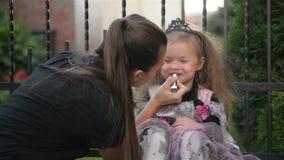 Woman preparing her daughter to halloween. Young cutie girl having fun. Happy halloween stock video footage