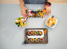 Woman preparing horribly halloween treats for party. Closeup. Kids will be stunned! Closeup on woman in kitchen preparing horribly tasty delicious halloween Stock Images
