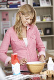 Woman Preparing Ingredients To Bake Cakes In Kitchen Royalty Free Stock Photos
