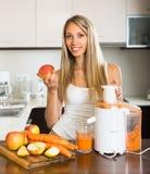 Woman preparing juice in kitchen Stock Photo