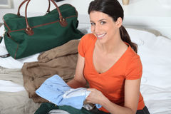 Woman preparing luggage. Woman packing green weekend bag Royalty Free Stock Photo