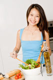 Woman Preparing Meal. A good looking woman preparing a healthy meal of bread and salad in her kitchen at home stock photography
