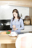 Woman preparing a meal in the kitchen. Beautiful young woman preparing the ingredients for a meal in her kitchen Royalty Free Stock Photography